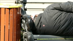 Homeless tramp beggar man sleeps on  city bench . Contrasts of e city .4K 3840x - stock footage