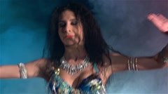 Middle section of a woman's body dancing belly dance, in smoke, slow motion Stock Footage