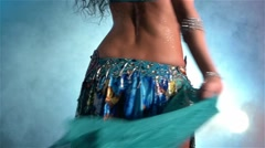 Middle section of a woman's body dancing belly dance, in smoke, whirling, slow Stock Footage