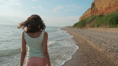Young slim woman walking along a deserted seashore in the summer Stock Footage