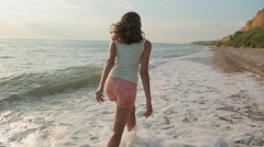Free girl running barefoot on the water along a deserted beach in the summer Stock Footage