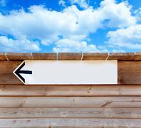 Aged wood arrow direction sign on blue sky Stock Photos