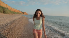Happy girl running along the beach barefoot and laughing, enjoying life Stock Footage
