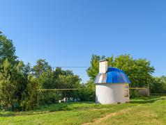 Small round house with blue domed roof on green lawn on sunny summer day - stock photo