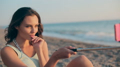 Sweet model sitting near the sea at sunset and makes selfie to the phone using a Stock Footage