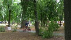 Man passing through the park, checking if rain falling and opening umbrella, 4k. Stock Footage