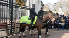 Two police officers riding a horse infront of the palace Stock Footage