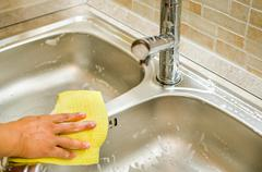 Woman hand doing chores in the kitchen at home , sink and faucet - stock photo