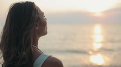 Beautiful woman smoking a cigarette at sunset near the sea Stock Footage