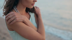 Thoughtful and beautiful girl standing near sea at sunset and looking ahead Stock Footage