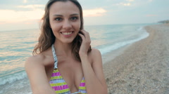 Lovely girl dressed in a swimsuit shoots herself on camera gopro near the sea Stock Footage