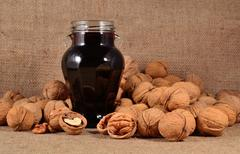 Jam from young walnuts in glass jar and walnuts - stock photo