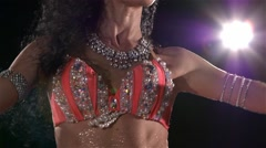 Young woman with long dark hair dancing belly dance, back light, slow motion - stock footage