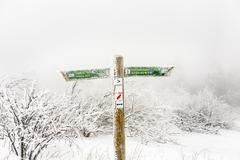 FELDBERG, GERMANY - JAN 4, 2015: post with signs for orientation and distance - stock photo