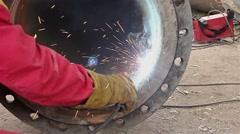 Welder is welding flange to the pipe. - stock footage