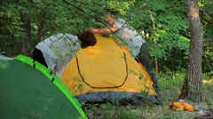 The girl and the man set the tent in the deciduous forest Stock Footage