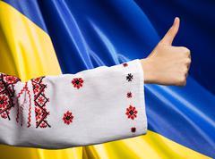 woman in Ukrainian clothes shows symbol ok against Ukrainian flag - stock photo
