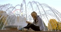 Girl reading near the fountain Stock Footage