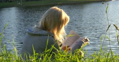 Blonde girl reading book on the lakeshore Stock Footage