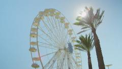 SLOW MOTION: Big ferris wheel spinning behind tall palms Arkistovideo
