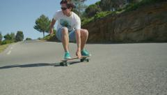 SLOW MOTION: Young man long boarding down the winding road Stock Footage