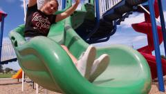Teenager having too much fun going down a slide Stock Footage
