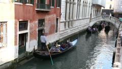 Shot of gondolas with tourists cruising through small Venetian canal Stock Footage