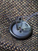 attaching of button to green tweed by needle - stock photo