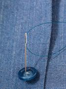 Attaching of button to blue silk dress by needle Stock Photos
