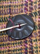 Attaching of button to woolen fabric by needle Stock Photos
