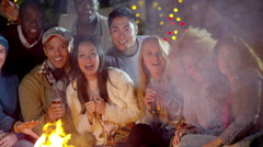4K Happy mixed ethnicity friends watching fireworks in front of open fire Stock Footage