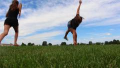 Girls running through the field doing cartwheels and flips Stock Footage