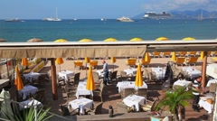 Restaurant on the Beach in Cannes with tables and chairs, France Stock Footage