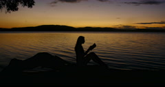 Female silhouette reading on branch overlooking the sea Stock Footage