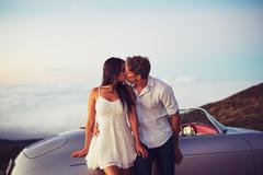 Couple Kissing with Classic Vintage Sports Car Stock Photos