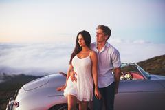 Couple Watching the Sunset with Classic Vintage Car Stock Photos