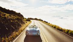 Stock Photo of Coupe Driving on Country Road in Vintage Sports Car