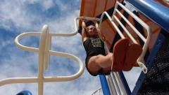 young girl having fun swinging back and forth from jungle gym at playground - stock footage