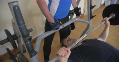 Bench pressing with gym instructor Stock Footage