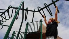 Young girl swinging from monkey bars at park Stock Footage