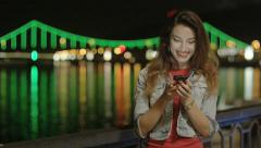 Cute Positive Female Texting and Messaging on the Phone at Night in the City - stock footage