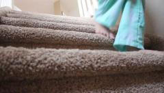 Low angle of girl in pajamas walking down carpeted stairs Stock Footage
