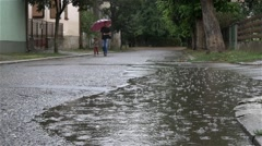 Father and little daughter with umbrella, rain falling in puddle, slow motion. - stock footage