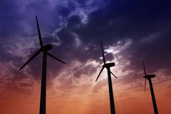 Aerogenerator windmills on dramatic sunset sky Stock Photos