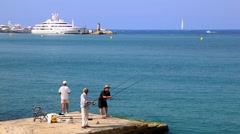 Fishing in the sea, tree fishermen in the water, Cannes, France Stock Footage