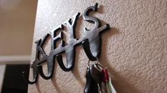 Hanging a set of keys up on a key rack Stock Footage