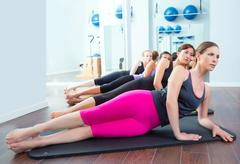Pilates women group lying on mat with gym instructor Stock Photos