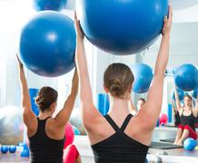 stability ball in women Pilates class rear view - stock photo