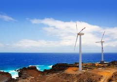 Aerogenerator windmills in front of ocean sea - stock photo