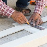 Carpenter using ruler to draw a line marking on a wood board Stock Photos